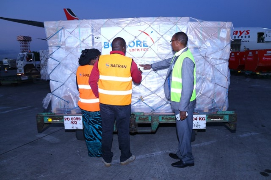 Safran Identity and Security officials Ms Lilian Owitti (left) and Chaka Simba (centre) flanked by Postal Corporation of Kenya Clearing and Forwarding Assistant Manager, Mr Wilson Yegon (right) verifying the shipment details on one of the KIEMS Electoral kits at JKIA.