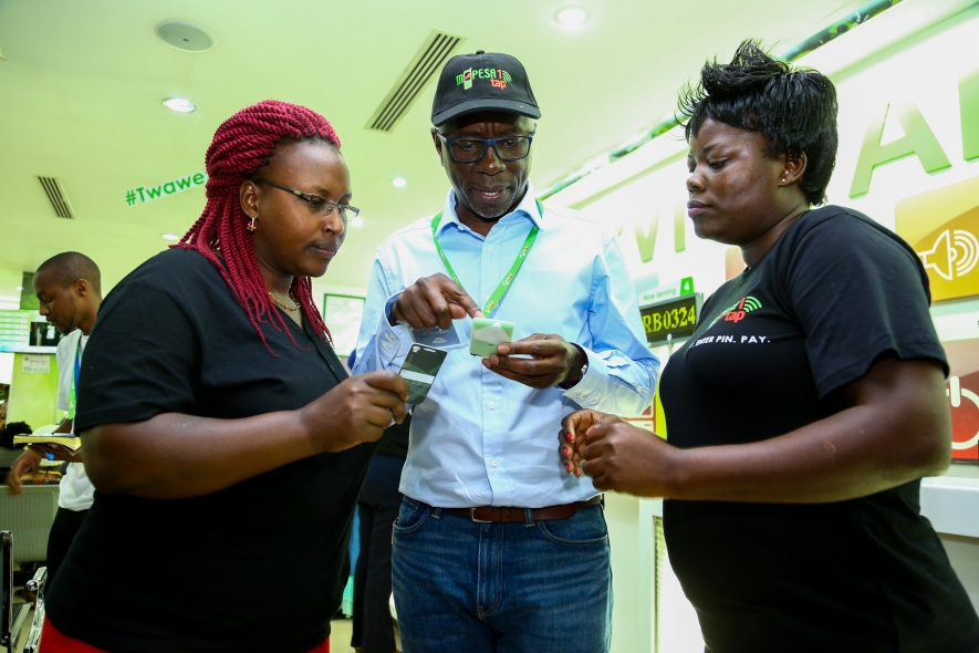 Director, Regional Operations and Sales Safaricom, Steve Okeyo with Seline Opondo Safaricom Nakuru Retail Center Manager explains how to use the M PESA 1 tap card to Beatrice Chepkemoi during the launch of the card in Nakuru.